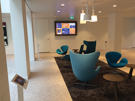 A Brickz.tv powered                             Rabobank lobby with a big screen and several tablets